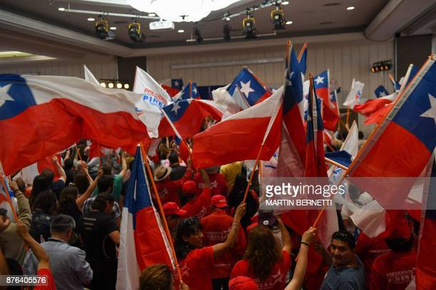 Supporters of Chilean presidential candidate Sebastian Pinera waves Chilean flags as they celebrate at the party headquarters in Santiago de Chile on...