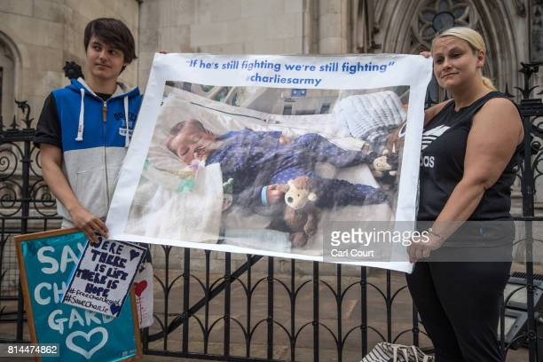 Supporters of Chris Gard and Connie Yates the parents of terminally ill toddler Charlie Gard hold a banner outside The Royal Courts of Justice on...