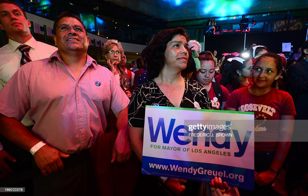 Supporters of City Controller Wendy Greuel, Sandra Flores (C) and Manuel Zitle (L), await her arrival after polls in a run-off election for Mayor closed in Los Angeles, California on May 21, 2013. Los Angeles councilman Eric Garcetti took a narrow lead in early results from a run-off election to succeed LA mayor Antonio Villaraigosa, but the race remained too close to call after midnight. Garcetti and Greuel, both Democrats like Villaraigosa, campaigned down to the wire after emerging from a March primary poll contested by a total of eight candidates. AFP PHOTO/Frederic J. BROWN