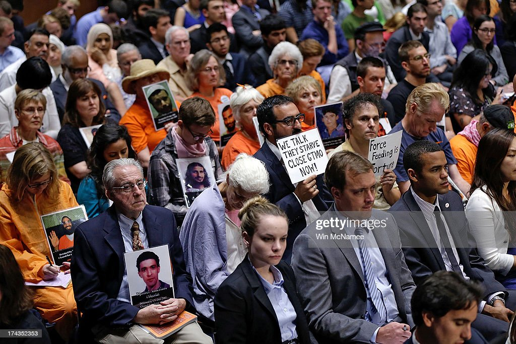 Supporters of closing the Guantanamo Bay Naval Base detention facility hold pictures of prisoners being held at the facility while viewing a hearing of the Senate Judiciary Committee July 24, 2013 in Washington, DC. The committee heard testimony from a panel of witnesses on 'Closing Guantanamo: The National Security, Fiscal, and Human Rights Implications.'