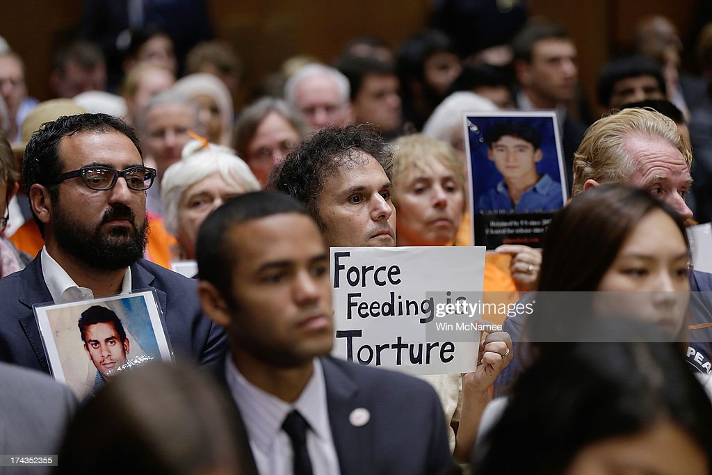 Supporters of closing the Guantanamo Bay Naval Base detention facility hold signs and pictures of prisoners being held at the facility while sitting in the audience during a hearing of the Senate Judiciary Committee July 24, 2013 in Washington, DC. The committee heard testimony from a panel of witnesses on 'Closing Guantanamo: The National Security, Fiscal, and Human Rights Implications.'