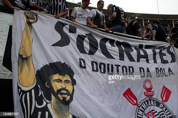 Supporters of Corinthians stand next to a huge banner in homage of the late footballer Socrates during the Brazilian Championship final date match...