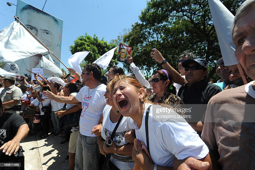 Supporters of deceased former general and presidential candidate of the UNACE party, Lino Oviedo -- who died along with his bodyguard Denis Galeano and pilot Ramon Picco Delmas in a helicopter crash on February 2-- cry at the passage of the hearse that carries his remains during his funeral in Asuncion, on February 6, 2013. Oviedo, 69, the controversial presidential candidate who helped topple Paraguayan dictator Alfredo Stroessner in 1989, died when the aircraft crashed en route to Asuncion while returning from a campaign rally in northern Paraguay, prompting claims of foul play. AFP PHOTO /Norberto Duarte