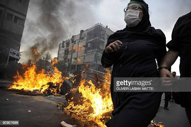 Supporters of defeated Iranian presidential candidate Mir Hossein Mousavi run past burning debris during riots in Tehran on June 13 2009 Hardline...