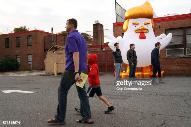 Supporters of Democrat Ralph Northam inflate a cartoon chicken made to resemble President Donald Trump outside the polling place at Washington Mill...