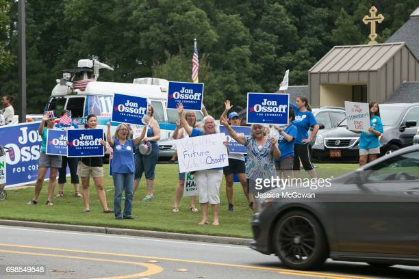 Supporters of Democratic candidate Jon Ossoff wave at cars passing by St Mary's Orthodox Church of Atlanta on June 20 2017 in Roswell Georgia Voters...