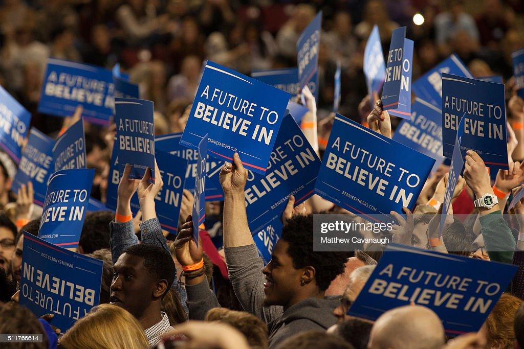 Supporters of democratic presidential candidate Sen Bernie Sanders wave signs at a rally at the University of Massachusetts on February 22 2016 in...