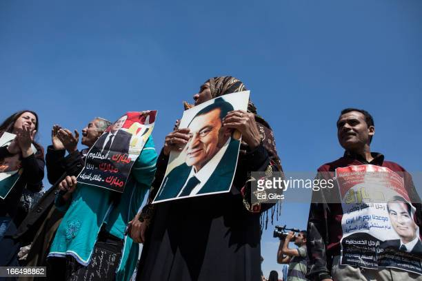Supporters of deposed Egyptian President Hosni Mubarak hold posters of the former dictator at the start of the retrial of Mubarak at the Cairo Police...