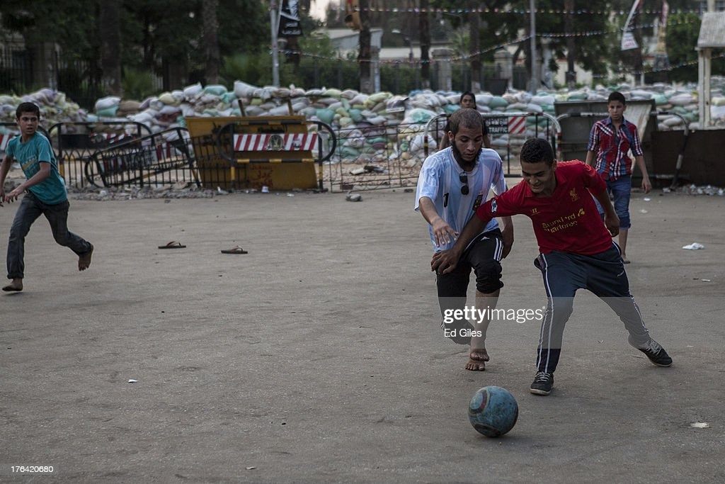 Supporters of deposed Egyptian President Mohammed Morsi play football at a sit-in demonstration at Nahda Square in the Giza district on August 12, 2013 in Cairo, Egypt. Egyptian security forces threatened to begin a siege of pro-Morsi protest camps in Cairo overnight on August 11, however Egypt's Interior Ministry appeared to have put off plans to crack down on protesters early on August 12. On Monday Egypt's judiciary also extended deposed President Morsi's detention for a further 15 days pending investigation into charges of his collaboration with the Palestinian Hamas movement. Morsi supporters have continued to protest at sites across Cairo over one month after the Egyptian military deposed Egypt's first democratically elected President, Mohammed Morsi, on July 3. (Photo by Ed Giles/Getty Images).