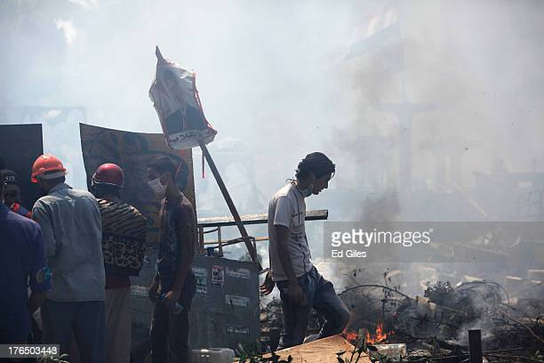 Supporters of deposed Egyptian President Mohammed Morsi stand amongst debris during a violent crackdown by Egyptian Security Forces on a proMorsi...
