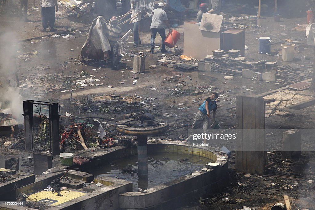 Supporters of deposed Egyptian President Mohammed Morsi throw rocks while taking cover among debris during a violent crackdown by Egyptian Security Forces on a pro-Morsi sit-in demonstration at the Rabaa al-Adweya Mosque in the Nasr City district on August 14, 2013 in Cairo, Egypt. An unknown number of pro-Morsi protesters were killed in Egypt's capital today as Egyptian Security Forces undertook a planned operation to clear Morsi supporters from two sit-in demonstrations in Cairo where they have camped for over one month. Egyptian Police and Army forces entered protest sites in the Nasr City and Giza districts at dawn using tear gas, live fire and bulldozers to disperse protesters and destroy the camps. A state of emergency has been declared in Egypt to begin this afternoon and will reportedly last for one month.