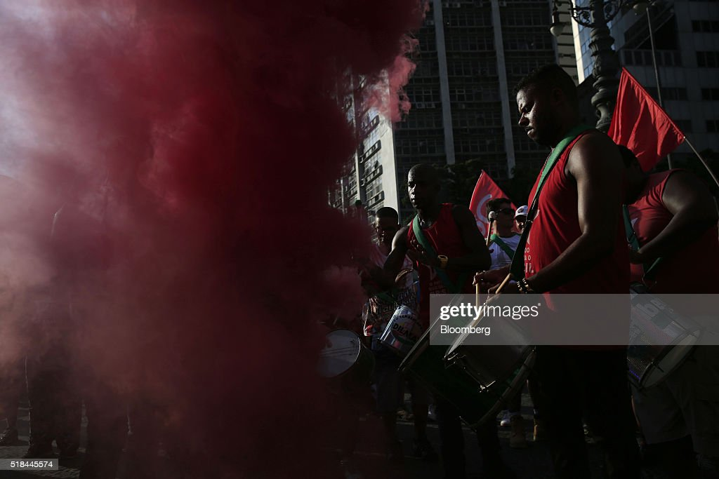 Supporters of Dilma Rousseff Brazil's president not pictured play drums near red smoke during a demonstration in Rio de Janeiro Brazil on Thursday...