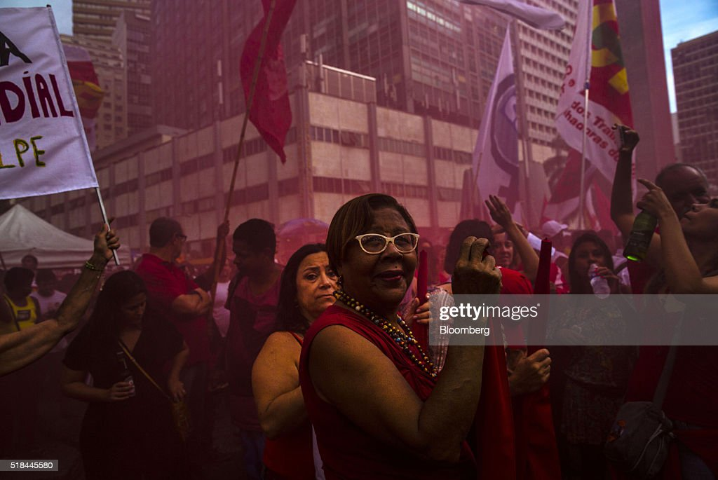 Supporters of Dilma Rousseff Brazil's president not pictured stand in red smoke during a demonstration in Rio de Janeiro Brazil on Thursday March 31...