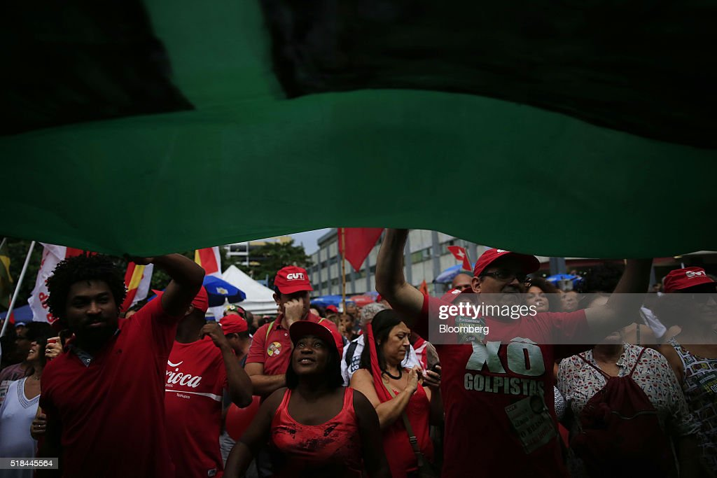 Supporters of Dilma Rousseff Brazil's president not pictured wave a yellow and green banner during a demonstration in Rio de Janeiro Brazil on...