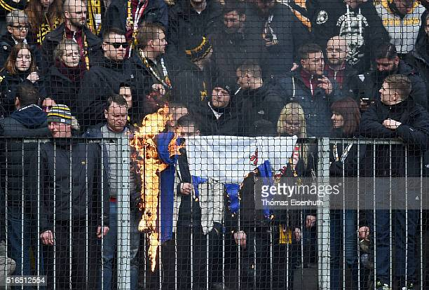 Supporters of Dresden burn supporter flags of Hansa Rostock after the Third League match between SG Dynamo Dresden and FC Hansa Rostock at DDVStadion...