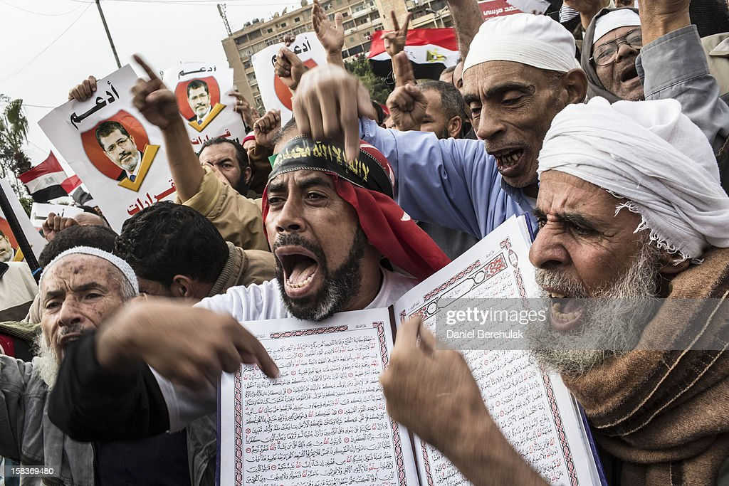 Supporters of Egyptian President Mohamed Morsi and members of the Muslim Brotherhood chant slogans during a rally on December 14 2012 in Cairo Egypt...