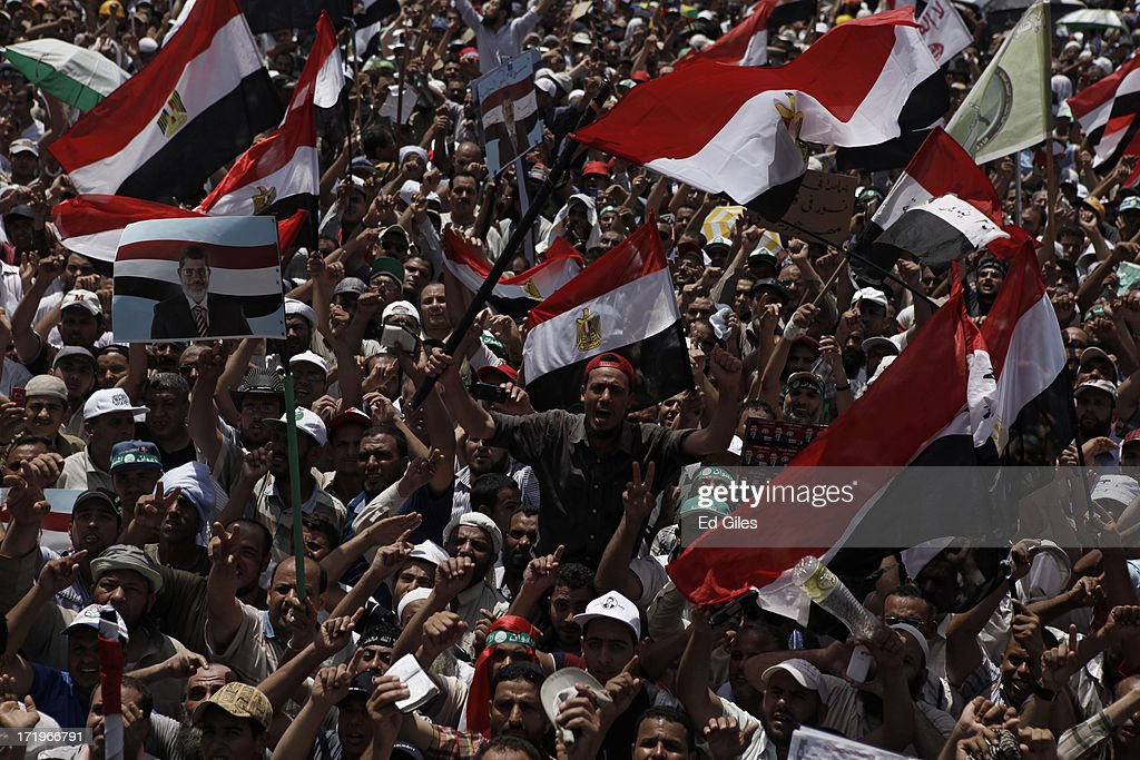 Supporters of Egyptian President Mohammed Morsi chant during a demonstration at the Rabaa al-Adaweya Mosque in the suburb of Nasr City on June 30, 2013 in Cairo, Egypt. Crowds of pro- and anti-Morsi protesters gathered in locations across Egypt today, as a series of nation-wide mass demonstrations entitled 'Tamarod,' or 'Rebel,' took place on the first anniversary of Morsi's election to the Egyptian Presidency. The 'Tamarod' campaign, organised by a coalition of opposition political groups, aims to bring down the government of President Morsi through country-wide demonstrations.