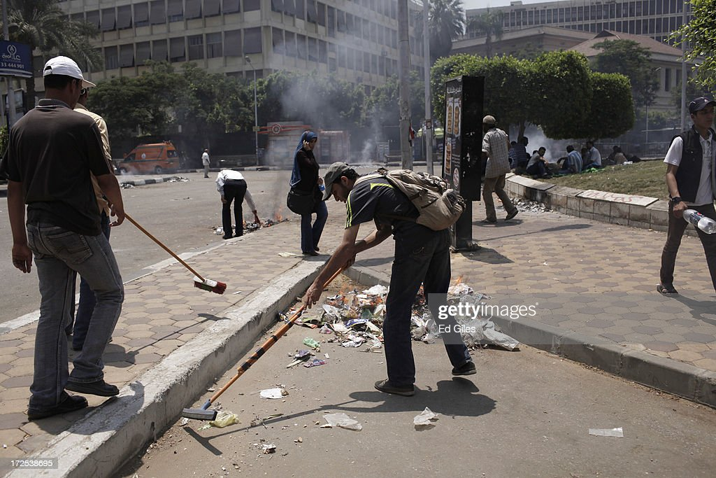 Supporters of Egyptian President Mohammed Morsi clean up debris after violent clashes at Cairo University the previous night, on July 3 2013, in Cairo, Egypt. The Egyptian Health Ministry reported at least 16 people were killed overnight on July 2 in violent clashes between Pro-Morsi and Anti-Morsi protesters in the Cairo suburb of Giza. An Army ultimatum to President Morsi comes to an end on Wednesday afternoon. In a statement on July 1, the Egyptian Army asked Egyptian President Mohammed Morsi to resolve mass demonstrations against his continued rule or face intervention by the military within 48 hours, after millions of Egyptians took to the streets to protest Morsi's rule on June 30. (Photo by Ed Giles/Getty Images).