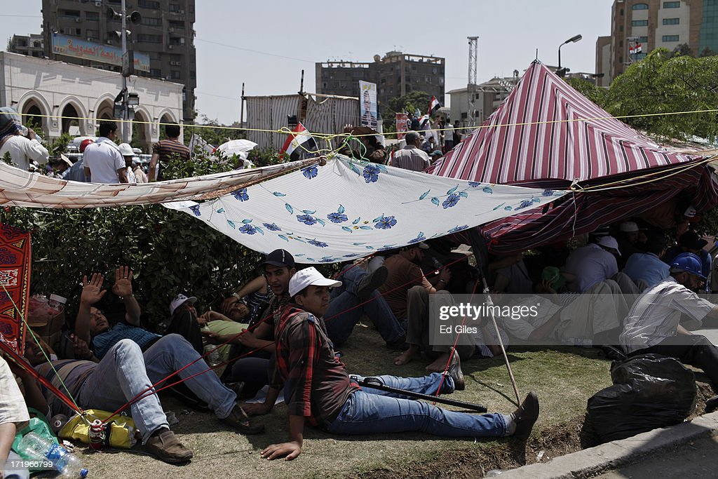 Supporters of Egyptian President Mohammed Morsi sit in under cloths put up for shade during a demonstration at the Rabaa alAdaweya Mosque in the...