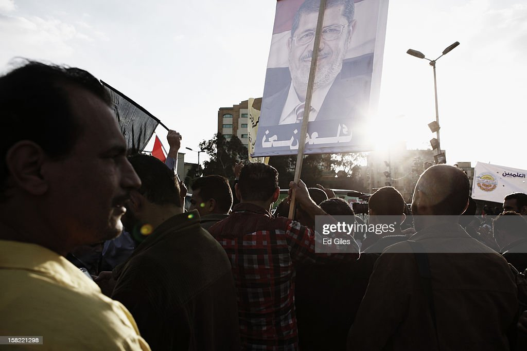 Supporters of Egyptian President Mohammed Morsi take part in a demonstration in the Cairo suburb of Nasser City on December 11, 2012 in Cairo, Egypt. Both Anti-Morsi and Pro-Morsi demonstrations continue across Egypt over the country's draft constitution, rushed through parliament in an overnight session on November 29. The country's new draft constitution, passed by a constitutional assembly dominated by Islamists, will go to a referendum on December 15. (Photo by Ed Giles/Getty Images).