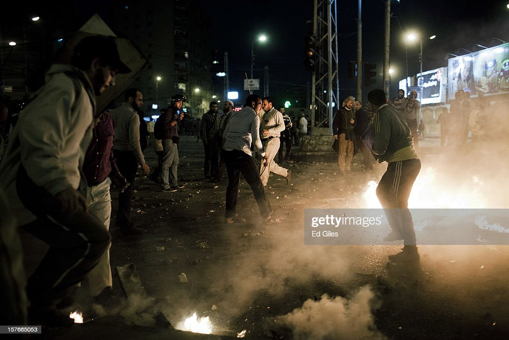 Supporters of Egyptian President Mohammed Morsi try to put out fires lit during clashes with anti-Morsi protesters near Egypt's Presidential Palace on December 5, 2012 in Cairo, Egypt. Reports indicate at least two people were killed in the Cairo suburb of Heliopolis after thousands of protesters from groups both supporting and against President Morsi converged on the Presidential Palace on the evening of December 5, after large anti-government demonstrations in front of the palace on December 4. Anti-Morsi protesters continue to demonstrate across Egypt against the country's draft constitution, rushed through parliament in an overnight session on November 29. The country's new draft constitution, passed by a constitutional assembly dominated by Islamists, will go to a referendum on December 15. (Photo by Ed Giles/Getty Images).