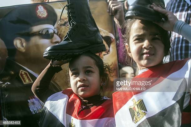 Supporters of Egypt's army chief Field Marshal Abdel Fattah alSisi who is to run for the presidency in the upcoming elections hold military boots on...