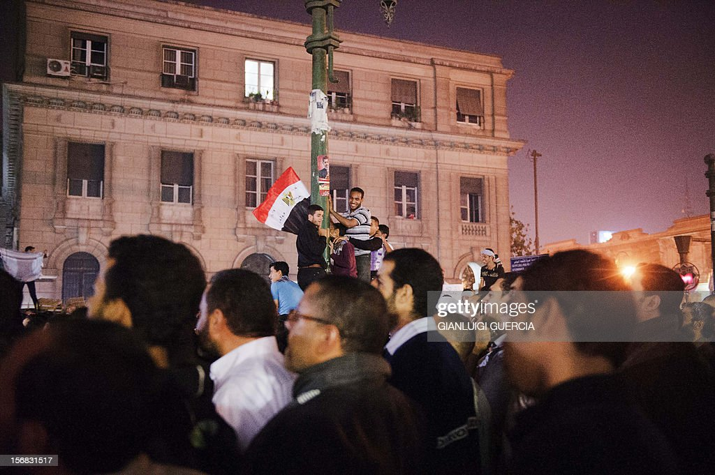 Supporters of Egypt's President Mohamed Morsi wave their national flag as they celebrate in front of the Egyptian high court in Cairo on November 22, 2012, after Morsi assumed sweeping powers, putting him on a collision course with the judiciary and raising questions about the country's democratic future. The move, just a day after Morsi took diplomatic centre stage in brokering a ceasefire between Israel and Gaza's Islamist Hamas rulers, earnt him the same derisive monicker of 'new phararoh' levelled at veteran strongman Hosni Mubarak before his ouster in a popular uprising last year.