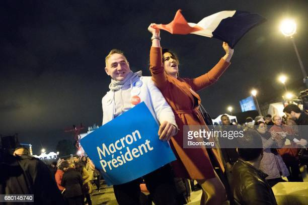 Supporters of Emmanuel Macron French presidentelect wave a French national flag and hold a sign in front of the Pyramid at the Louvre Museum after...
