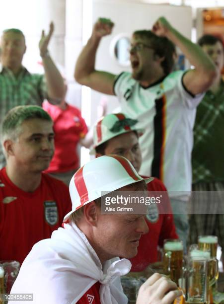 Supporters of England and Germany react at the 'Fox and Hound' English pub after Germany scored their site's second goal during the 2010 FIFA Word...