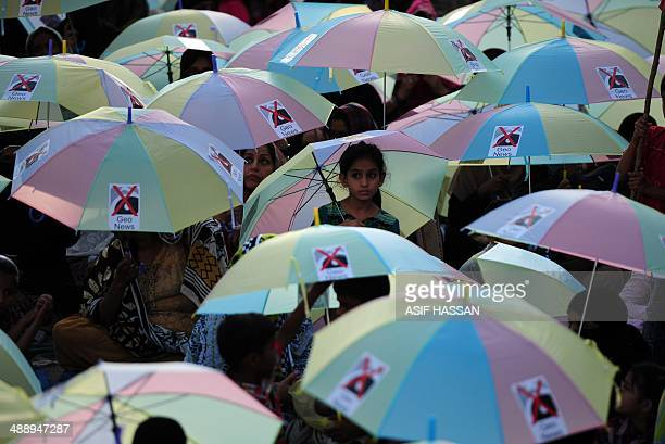 Supporters of ethnicbased party Mohajir Qaumi Movement hold umbrellas with logos against Geo TV outside the television network's building during a...