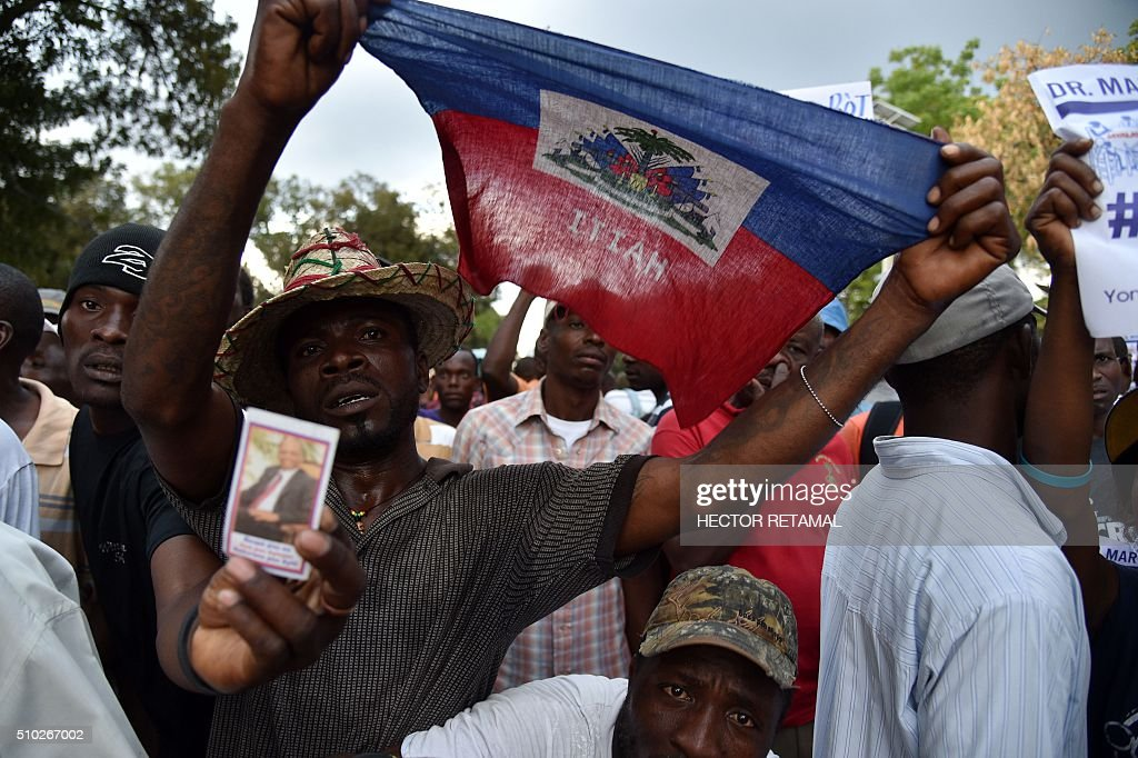 Supporters of Fanmi Lavalas political party manifest in front of the National Palace in Port-au-Prince, on February 14, 2016 to support newly elected Haitian Provisional President Jocelerme Privert. Haitian lawmakers early Sunday elected Jocelerme Privert as the troubled country's interim president to fill a power vacuum following the departure of Michel Martelly, after a vote to choose his successor was postponed over fears of violence. Privert, 62, a senator and president of the National Assembly, was chosen on the second round of balloting after a lengthy session that stretched overnight Saturday to Sunday. RETAMAL