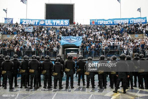 Supporters of FC Zenit St Petersburg are seen in the stands along with a riot policemen in the foreground during the Russian Football League...