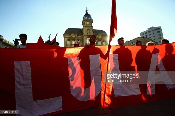 Supporters of former Brazilian president Luis Inacio Lula da Silva hold a giant banner with his name during a demonstration at Generoso Marques...