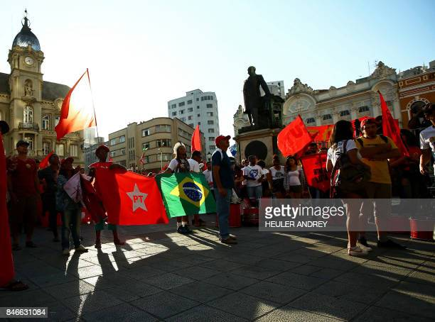 Supporters of former Brazilian president Luis Inacio Lula da Silva hold Workers Party and Brazilian flags during a demonstration at Generoso Marques...