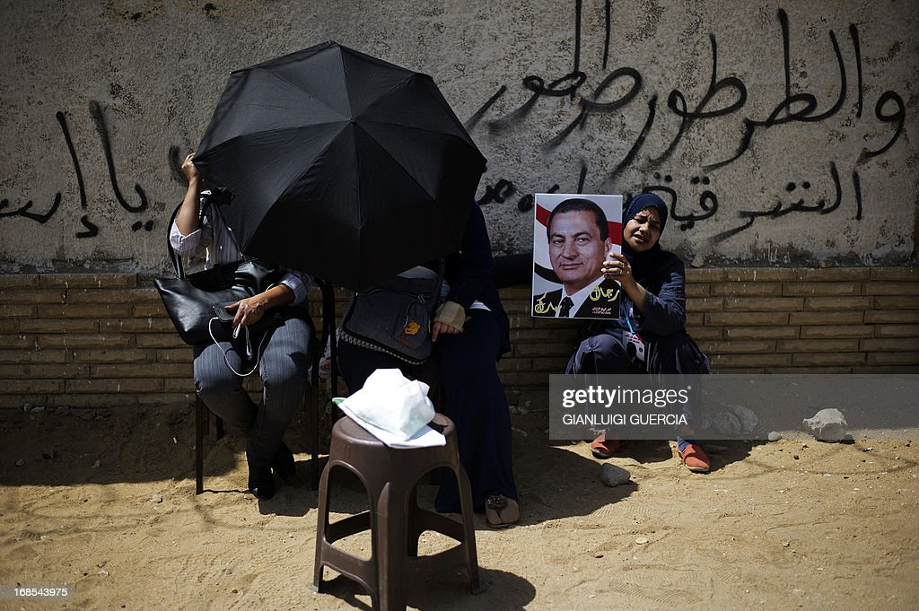 Supporters of former Egyptian president Hosni Mubarak, hold his portrait and shout slogans outside the Egyptian police academy in Cairo, where Mubarak's trial is taking place on May 11, 2013. Former Egyptian president Hosni Mubarak appeared in court to face a new trial for complicity in the murder of hundreds protesters during the 2011 uprising.