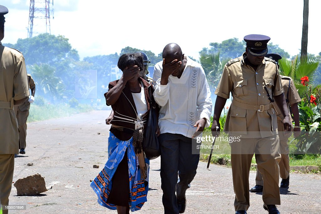 Supporters of former Foreign Affairs minister flee tear gas on March 11, 2013 during a demonstration in Blantyre. Malawi police on March 11 arrested 11 ex-ministers and senior government officials, including the former president's brother, for an alleged coup plot, sparking protests met with police tear gas.