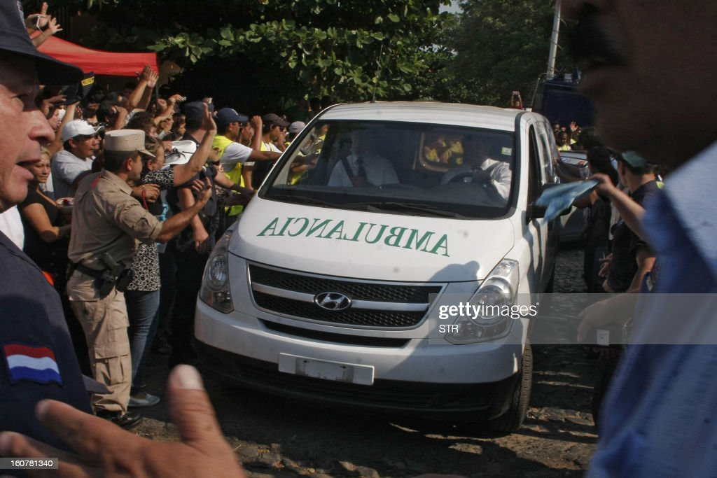 Supporters of former general and UNACE party presidential candidate Lino Oviedo --who died along with his bodyguard Denis Galeano and pilot Ramon Picco Delmas in a helicopter crash on February 2-- surround an ambulance carrying his coffin outside the morgue in Asuncion on February 5, 2013. Oviedo, 69, the controversial presidential candidate who helped topple Paraguayan dictator Alfredo Stroessner in 1989, died when the aircraft crashed en route to Asuncion while returning from a campaign rally in northern Paraguay, prompting claims of foul play. AFP PHOTO / STR