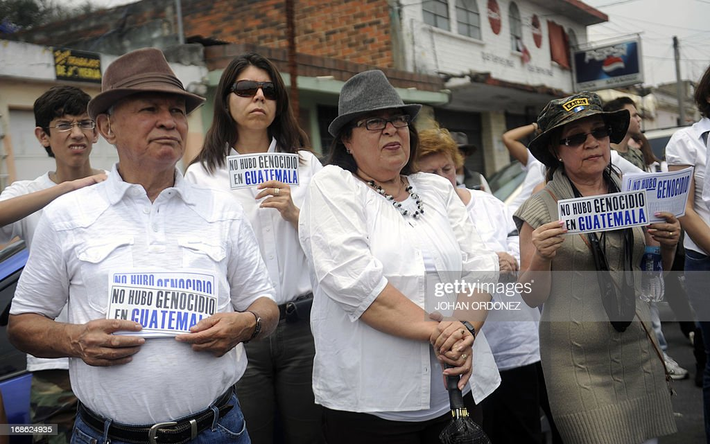 Supporters of former Guatemalan de facto President (1982-1983), retired General Jose Efrain Rios Montt, hold signs reading 'There was no genocide in Guatemala', during a protest outside a military prison at Matamoros in Guatemala city on May 12, 2013. Rios Montt was found guilty of genocide and war crimes on May 10 and sentenced to 80 years in prison in a landmark ruling stemming from massacres of indigenous people in his country's long civil war. Rios Montt thus became the first Latin American convicted of trying to exterminate an entire group of people in a brief but particularly gruesome stretch of a war that started in 1960, lasted 36 years and left around 200,000 people dead or missing. AFP PHOTO / Johan ORDONEZ