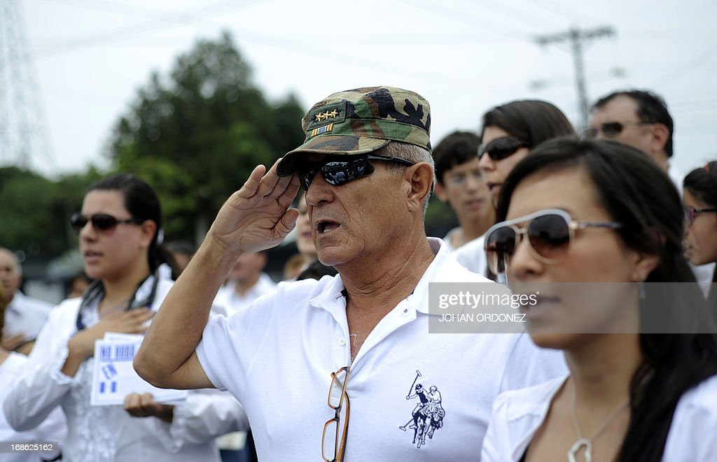 Supporters of former Guatemalan de facto President (1982-1983), retired General Jose Efrain Rios Montt, sing the national anthem during a protest against the latter's prosecution, outside a military prison at Matamoros in Guatemala City on May 12, 2013. Rios Montt was found guilty of genocide and war crimes on May 10 and sentenced to 80 years in prison in a landmark ruling stemming from massacres of indigenous people in his country's long civil war. Rios Montt thus became the first Latin American convicted of trying to exterminate an entire group of people in a brief but particularly gruesome stretch of a war that started in 1960, lasted 36 years and left around 200,000 people dead or missing. AFP PHOTO / Johan ORDONEZ