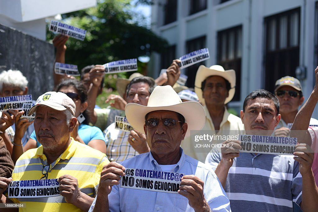 Supporters of former Guatemalan de facto President (1982-1983) retired General Jose Efrain Rios Montt hold signs reading 'The Guatemalans we are not genocidal' during a protest against the latter's prosecution, outside the Constitutional Court in Guatemala City on May 15, 2013. Rios Montt was found guilty of genocide and war crimes on May 10 and sentenced to 80 years in prison in a landmark ruling stemming from massacres of indigenous people in his country's long civil war. Rios Montt thus became the first Latin American convicted of trying to exterminate an entire group of people in a brief but particularly gruesome stretch of a war that started in 1960, lasted 36 years and left around 200,000 people dead or missing. AFP PHOTO / Johan ORDONEZ