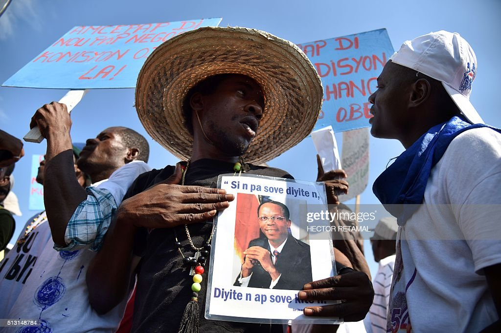 TOPSHOT Supporters of former Haitian president Jean Bertrand Aristide march in front of the Haitian Parliament in PortauPrince on February 29 2016 to...