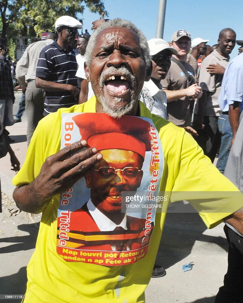 Supporters of former Haitian president Jean-Bertrand Aristide demonstrate on January 3, 2013 in front of the court during his subpoena by a judge in Port-au-Prince. Former president of Haiti Jean-Bertrand Aristide, the subject of several lawsuits for 'economic crimes, theft, breach of trust and criminal conspiracy' was called for justice on Thursday, according to judicial sources. AFP PHOTO Thony BELIZAIRE