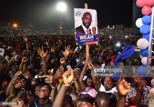 Supporters of former international Liberian football star turned politician George Weah wave during a presidential campaign rally in Monrovia on...