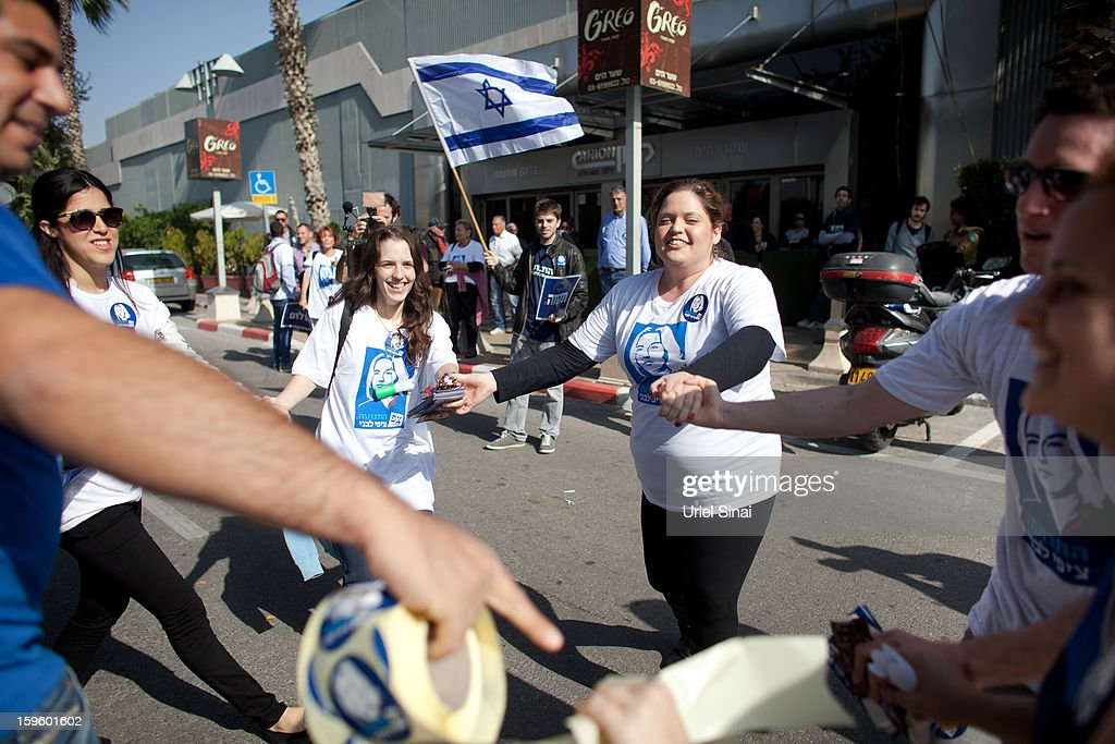 Supporters of former Israeli foreign minister Tzipi Livni, the leader of new party, The Movement, join hands ahead of an election event at a shopping center on January 17, 2013 in Ramat Gan, Israel. Israel will go to the polls on January 22.