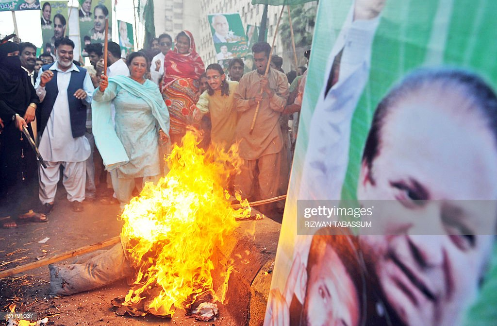 Supporters of former Pakistani premier Nawaz Sharif's Pakistan Muslim League-Nawaz (PML-N) party burn an effigy of former president Pervez Musharraf during a protest in Karachi October 12, 2009. The PML-N observes October 12 as a black day in commemoration of Musharraf's coup against the Sharif's government in 1999. Sharif was first elected prime minister in 1990 but was sacked three years later on corruption charges. He returned to power in 1997, but was ousted in the 1999 coup by Musharraf, who brought criminal charges against him for hijacking, terrorism and attempted murder. AFP PHOTO/ Rizwan TABASSUM