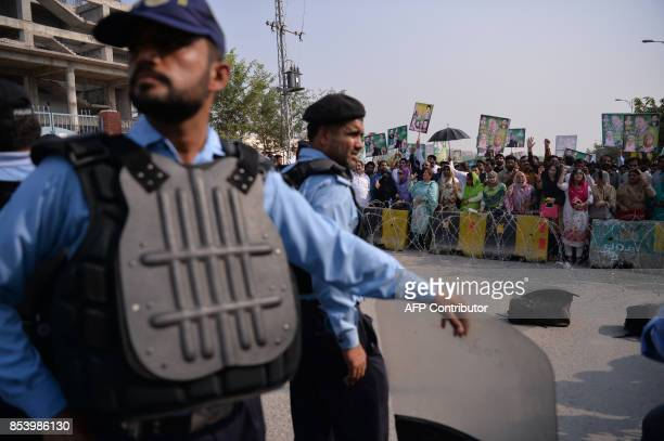 TOPSHOT Supporters of former Pakistani prime minister Nawaz Sharif hold placards as they shout slogans outside an accountability court where Sharif...