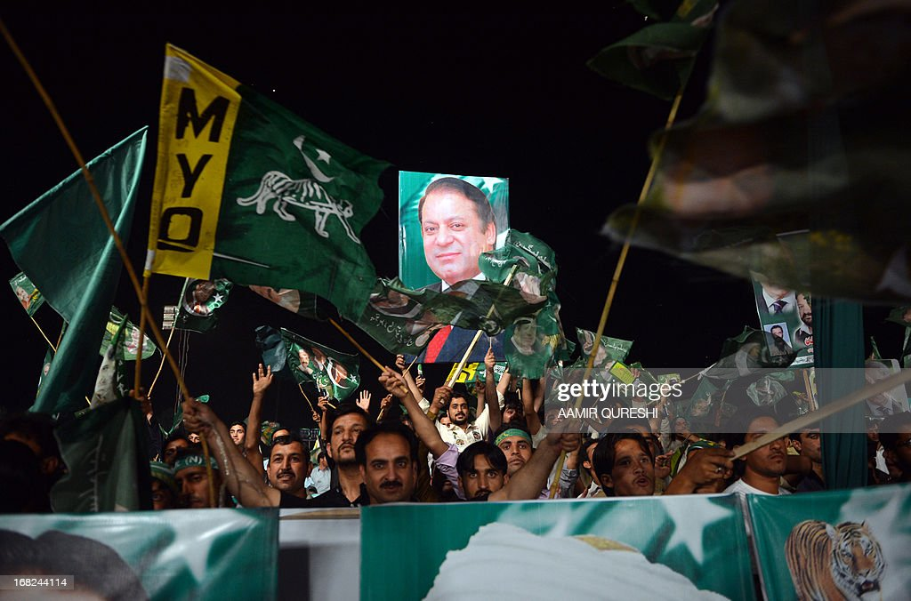 Supporters of former Pakistani Prime Minister Nawaz Sharif wave their party flags during an election campaign meeting in Rawalpindi on May 7, 2013. The election will mark a democratic milestone in a country ruled for half its history by the military. It will be the first time that a civilian government has served a full term and handed over to another at the ballot box. AFP PHOTO / AAMIR QURESHI