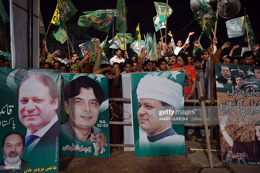 Supporters of former Pakistani Prime Minister Nawaz Sharif wave their party flgas during an election campaign meeting in Rawalpindi on May 7, 2013. The election will mark a democratic milestone in a country ruled for half its history by the military. It will be the first time that a civilian government has served a full term and handed over to another at the ballot box. AFP PHOTO / AAMIR QURESHI