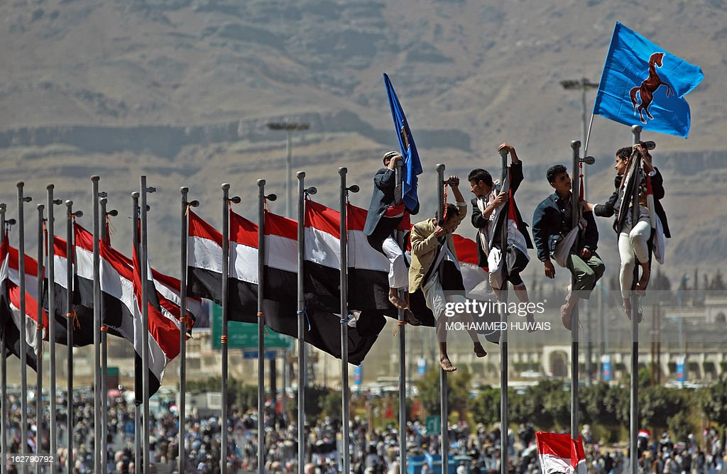 Supporters of former Yemeni president Ali Abdullah Saleh climb up flag poles flying their national flag during celebrations on the occasion of the first anniversary of the handover of power in Sanaa on February 27, 2013. Saleh stepped down after 33-years at the helm in February 2011 and formally handed power to his then deputy, Abdrabuh Mansur Hadi. AFP PHOTO/ MOHAMMED HUWAIS