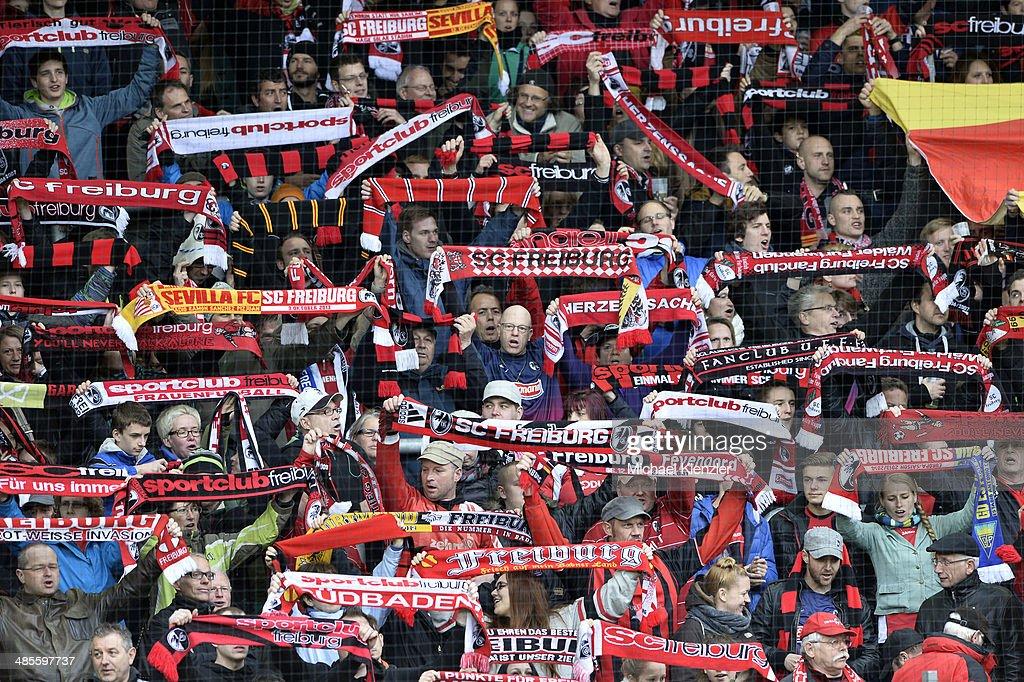 Supporters of Freiburg singing before the Bundesliga match between SC Freiburg and Borussia Moenchengladbach at Mage Solar Stadium on April 19, 2014 in Freiburg, Germany.
